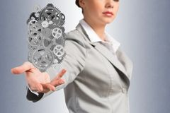 Business woman holds up a mechanism of gears Stock Photos