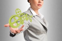 Business woman holds up a mechanism of gears Royalty Free Stock Image