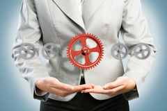 Business woman holds up a mechanism of gears Royalty Free Stock Photography