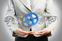 Business woman holds up a mechanism of gears Royalty Free Stock Images