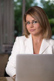 Business woman at home. Business woman seating behind laptop Stock Images