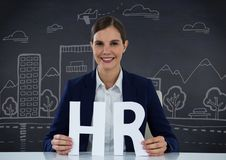 Business woman with HR letters against navy chalkboard with white city doodles Royalty Free Stock Photos