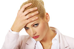 Business woman with a huge headache holding head Royalty Free Stock Photos