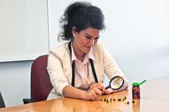 Business woman inspect medicine with magnifier. Business woman is carefully examine and inspect medicine with magnifier Royalty Free Stock Image