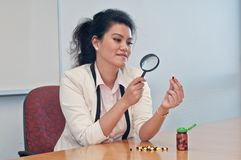Business woman inspect medicine with magnifier. And decide whether to take the capsule Royalty Free Stock Photography
