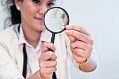 Business woman inspect medicine with magnifier. Smile to inspect the capsule in her fingers Stock Photos