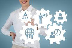 Business woman interacting with people in cogs graphics against blue background. Digital composite of Business woman interacting with people in cogs graphics Stock Photo