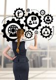 Business woman interacting with people in cogs graphics against office background. Digital composite of Business woman interacting with people in cogs graphics Royalty Free Stock Image
