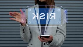 Business woman interacts HUD hologram Risk. Unrecognizable business woman, interacts with a HUD hologram with text Risk. Girl in a business suit uses the stock footage