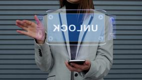 Business woman interacts HUD hologram Unlock. Unrecognizable business woman, interacts with a HUD hologram with text Unlock. Girl in a business suit uses the stock video