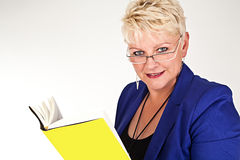 Business woman in jacket with glasses reading a book Stock Photos