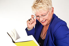 Business woman in jacket with glasses reading a book Royalty Free Stock Photos