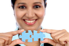 Business woman joining two jigsaw puzzle pieces Stock Photo