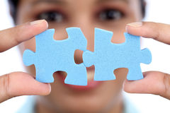 Business woman joining two jigsaw puzzle pieces Royalty Free Stock Image