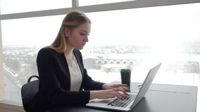 Business woman typing on laptop computer at workplace in modern office. Business woman journalist blogger typing text on laptop computer at workplace in modern stock footage