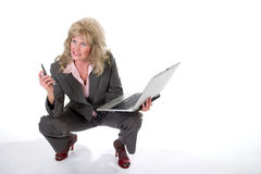 Business Woman Juggling Cellphone and Laptop. Attractive business trying to work on her laptop while dealing with her cellphone Royalty Free Stock Photo