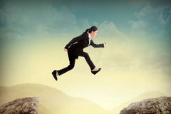 Business woman jump to another peak of mountain Stock Images