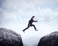 Business woman jumping across hill Stock Photography