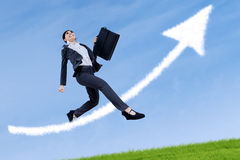 Business woman jumping with arrow sign Royalty Free Stock Images