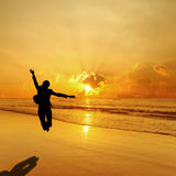 Business Woman Jumping in beach and Sea Sunset Royalty Free Stock Image