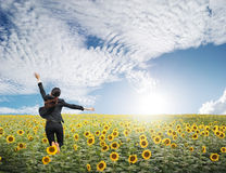 Business woman jumping in blue sky over sunflowers field stock photo
