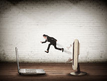 Business woman jumping from desktop computer to laptop Royalty Free Stock Images