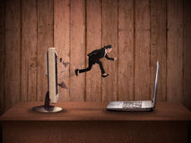 Business woman jumping from desktop computer to laptop Stock Photo