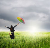 Business woman jumping holding rainbow umbrella in green rice fields and raincloud Royalty Free Stock Photography