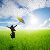 Business woman jumping holding rainbow umbrella in green rice fields and sunset Stock Images