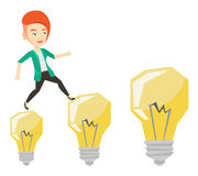 Business woman jumping on light bulbs. Stock Photo
