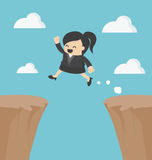 Business Woman jumping over the cliff Stock Image