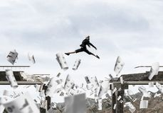 Problems and difficulties overcoming concept. Business woman jumping over gap in bridge among flying papers as symbol of overcoming challenges. Skyscape and Stock Images