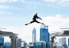 Problem and difficulties overcoming concept. Business woman jumping over gap in concrete bridge as symbol of overcoming challenges. Cityscape on background. 3D Royalty Free Stock Photos