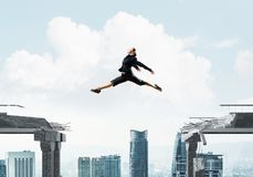 Problem and difficulties overcoming concept. Business woman jumping over gap in concrete bridge as symbol of overcoming challenges. Cityscape on background. 3D Royalty Free Stock Photo