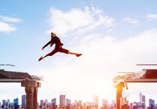 Problem and difficulties overcoming concept. Business woman jumping over gap in concrete bridge as symbol of overcoming challenges. Cityscape with sunlight on Stock Photography