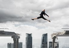 Problem and difficulties overcoming concept. Business woman jumping over gap in concrete bridge as symbol of overcoming challenges. Dark sky and cityscape on Stock Photography