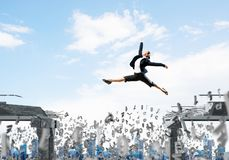 Problem and difficulties overcoming concept. Business woman jumping over gap with flying letters in concrete bridge as symbol of overcoming challenges Royalty Free Stock Photo