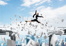 Problem and difficulties overcoming concept. Business woman jumping over gap with flying paper documents in concrete bridge as symbol of overcoming challenges Royalty Free Stock Images