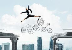 Problem and difficulties overcoming concept. Business woman jumping over gap with gear mechanism in concrete bridge as symbol of overcoming challenges Stock Photos