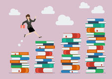 Business woman jumping over higher stack of books Royalty Free Stock Image