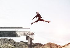 Problems and difficulties overcoming concept. Business woman jumping over huge gap in concrete bridge as symbol of overcoming challenges. Skyscape and nature Royalty Free Stock Images