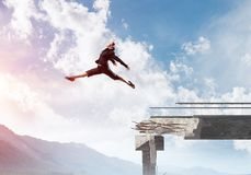 Problems and difficulties overcoming concept. Business woman jumping over huge gap in concrete bridge as symbol of overcoming challenges. Skyscape and nature Stock Photos