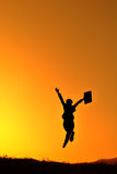 Business woman jumping and sunset silhouette Royalty Free Stock Photo