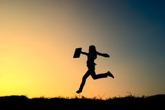Business woman jumping and sunset silhouette Royalty Free Stock Image