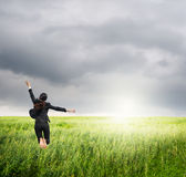 Business woman jumping to raincloud in grassland Stock Images