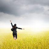 Business woman jumping to raincloud in grassland Royalty Free Stock Photography