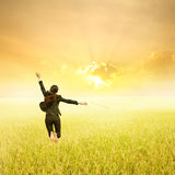 Business woman jumping in Yellow Rice fields and sunset on success day Stock Photo