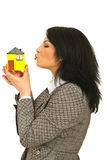 Business woman kissing miniature house Royalty Free Stock Photos