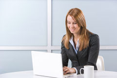 Business Woman on laptop. In a modern loft office Stock Image