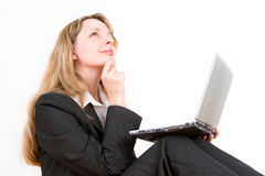 A business woman with a laptop. On her knees looking upwards and dreaming Stock Photos